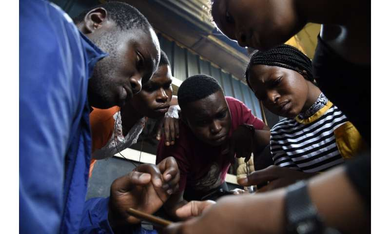 Code for Africa's John Eromosele, left, teaches volunteers how to use the app for the digital mapping project