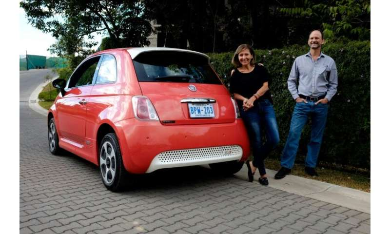Costa Rican Erick Orlich (R) and his wife Gioconda Rojas (L) run two electric cars powered by solar panels installed on the roof