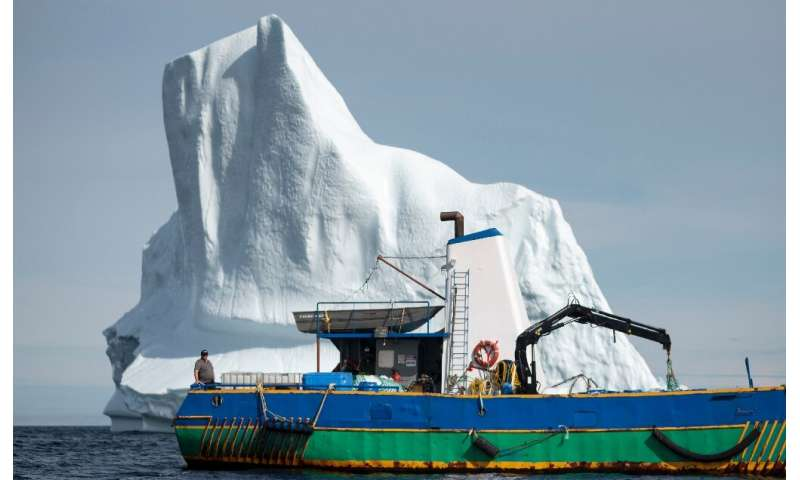 Edward Kean stands on his boat in front of an iceberg in Bonavista Bay, Newfoundland—he trades in iceberg water