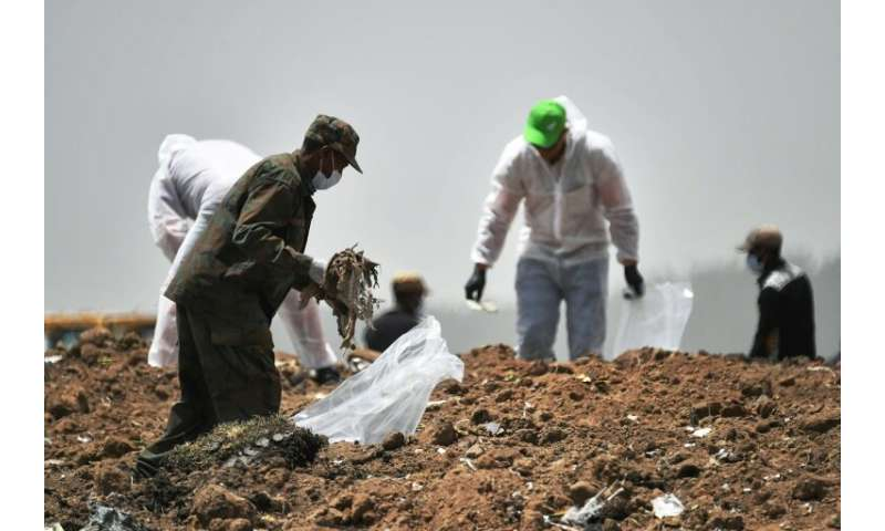 Forensic experts comb through the dirt for debris at the crash site of the Ethiopian Airlines Boeing 737 MAX 8 aircraft
