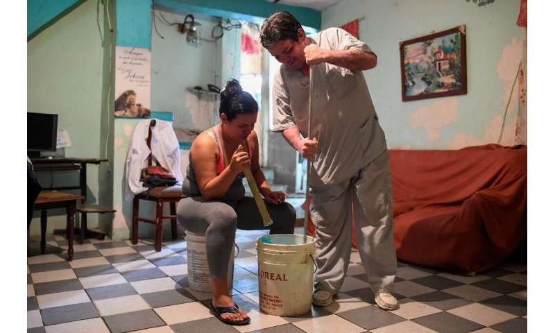 Francis Guillen and her father mix the chemicals to make the hairspray she will sell to supplement her meagre nurse's salary