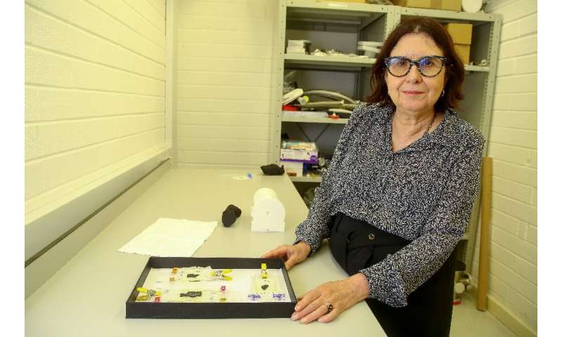 Francoise Berard, Director of the Library at the Institute de France, shows a box containing fragments of fragile Herculaneum sc