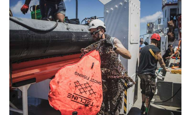 Ghost hunt: A Greenpeace crew member retrieves a device to identify abandoned nets and other fishing equipment. 'Ghost gear' is