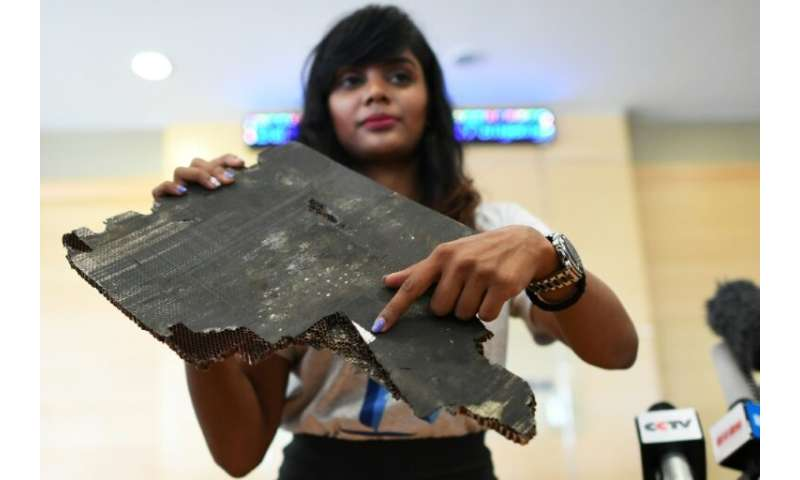 Grace Subathirai Nathan, daughter of Malaysian Airlines flight MH370 passenger Anne Daisy, shows debris believed to be from the