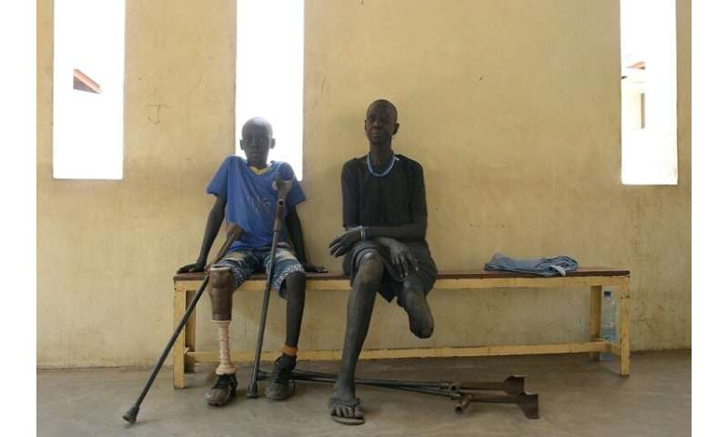 Gunshot wound survivors Jal Keat, 12, left, and Nyagn Thyuong, wait at the Red Cross rehabilitation centre in Juba