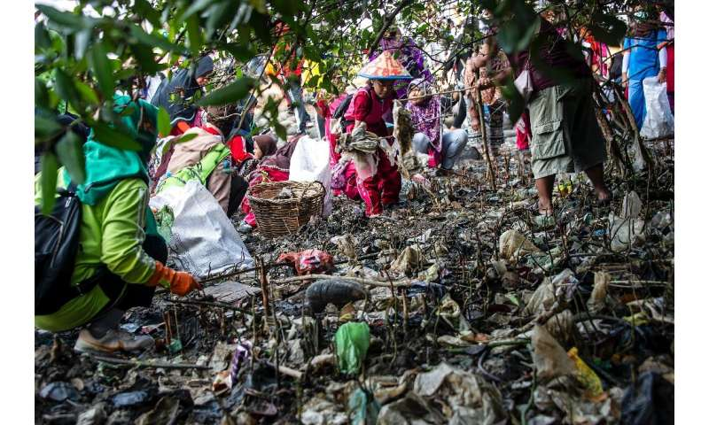 Indonesian children pick up litter from a beach in East Java province as part of World Cleanup Day