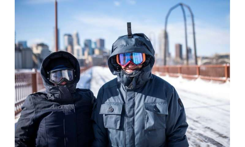 Jen Brackman and Aaron Brackman don heavy jackets and goggles while on a walk on the Stone Arch Bridge in Minneapolis, Minnesota