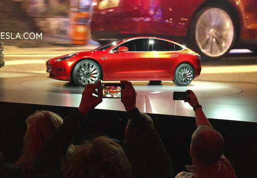 On the road to make an affordable car, Tesla cuts jobs