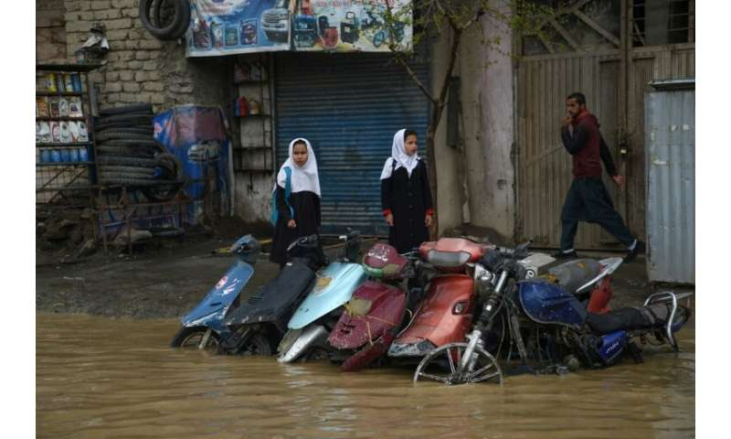 Pedestrians look for dry ground on a street after heavy rains in Kabul