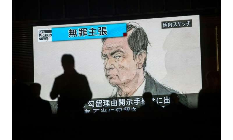 Pedestrians pass a screen displaying a sketch of former Nissan chief Carlos Ghosn in the Tokyo courtroom on Tuesday