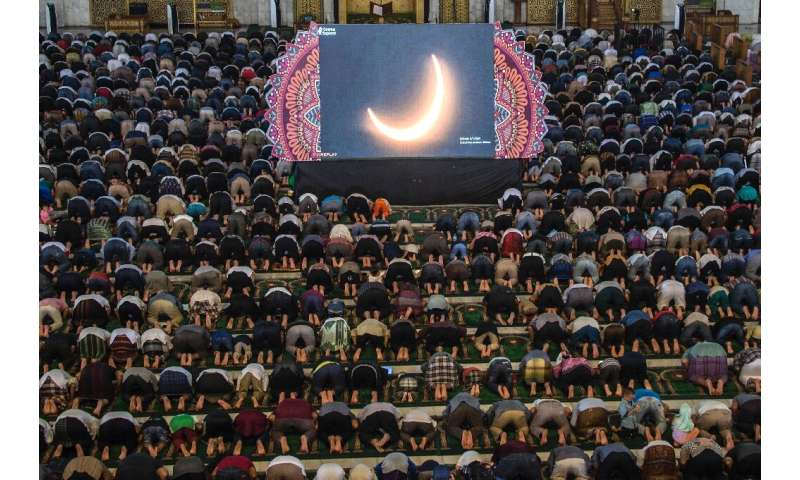 "People in Surabaya, Indonesia pray for the eclipse during the rare ""ring of fire"" solar eclipse"