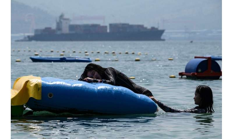 People swim at a beach in Subic Bay where a container ship hired by Canada is loaded with trash that the Philippines has ordered