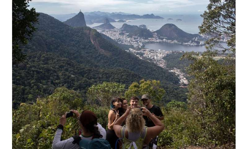 People take photos as they walk along a hiking trail above Rio de Janeiro—part of a projected 8,000-kilometer trail across Brazi