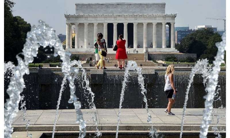 People walk near the World War II Memorial on the National Mall with the Lincoln Memorial in the background as temperatures soar