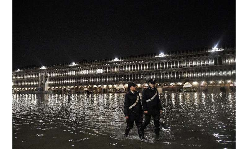 Police patrol flooded St. Mark's Square in Venice on November 12