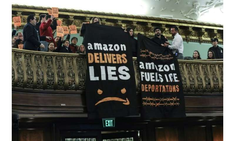 Protestors unfurl anti-Amazon banners from the balcony of a hearing room during a New York City Council finance committee hearin