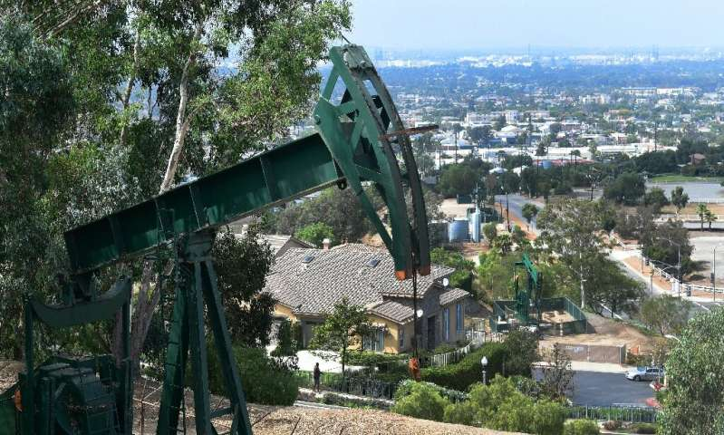 Pumpjacks in an oil well are seen on September 25, 2019 near Hilltop Park overlooking the city of Signal Hill, California, where
