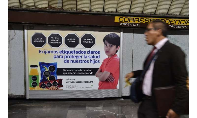 """We demand clear labeling to protect the health of our children,"" reads the sign in the Mexico City subway, which show"