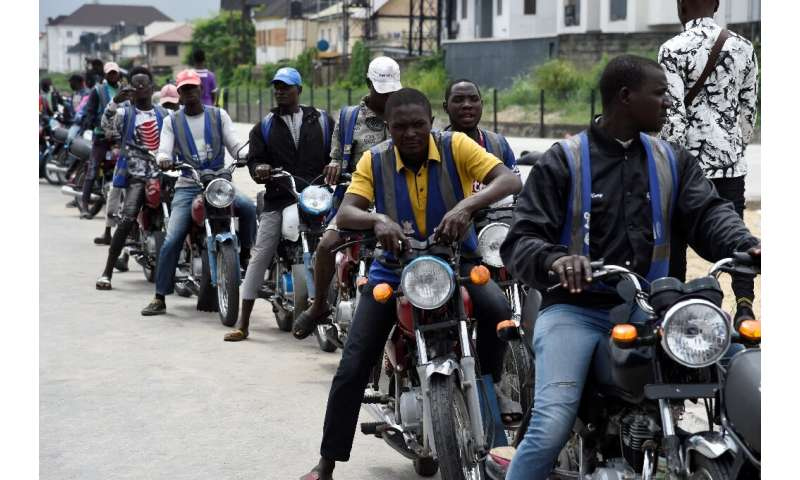 Regular motorcycle taxis queue for custom in Lagos—helmets and safety kits are absent, and passengers have to haggle over fares