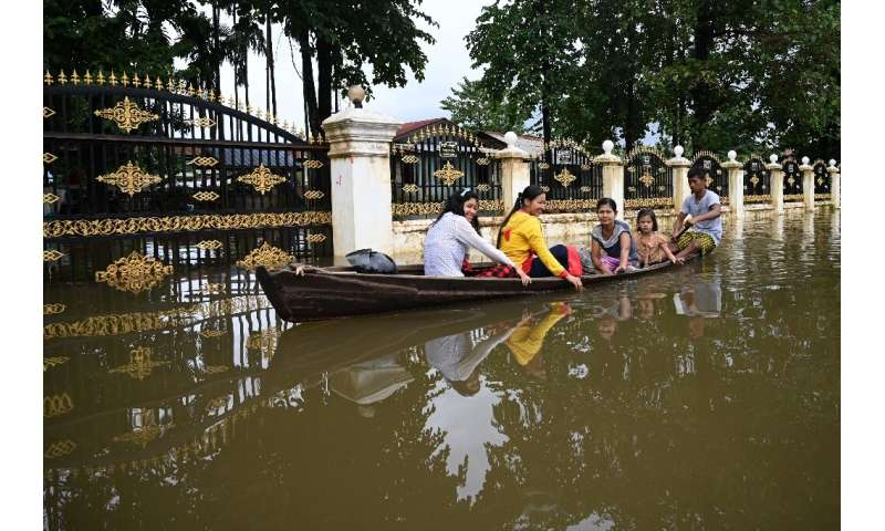 Residents ride in a boat through flooded streets in Shwegyin township in the Bago Region of Myanmar