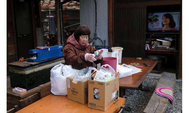 Saeko Takahashi, 71, separates trash into different boxes at her home in Kamikatsu and uses a compost bin for food waste
