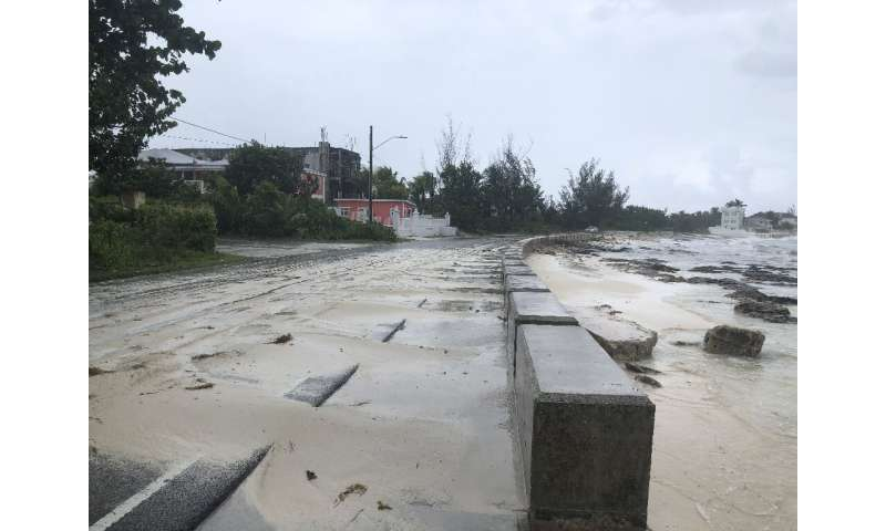 Sand pours onto a road near the beach in Nassau, Bahamas during the approach of Hurricane Dorian