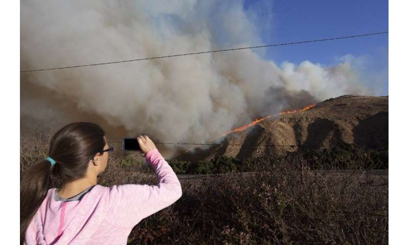SIMI VALLEY, CA - OCTOBER 30: A woman looks on as the Easy Fire approaches on October 30, 2019 near Simi Valley, California.