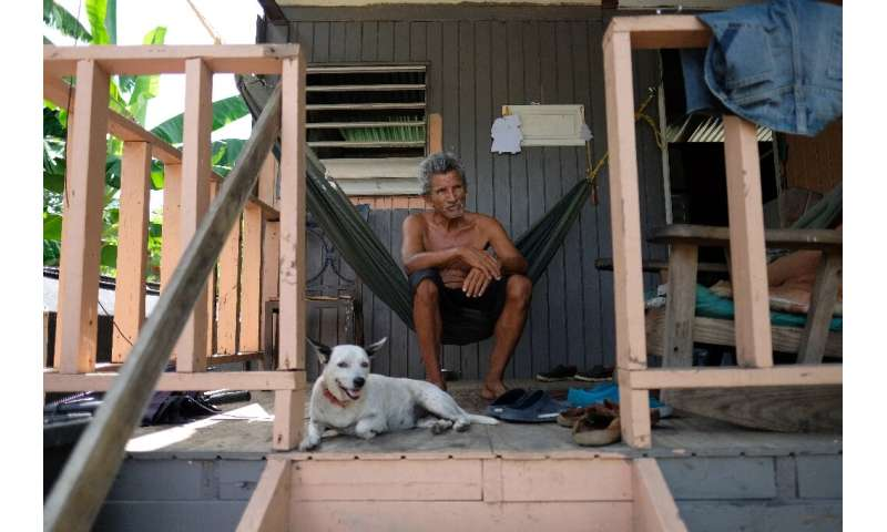 Sixto Marrero sits on the porch of his home in Puerto Rico, two years after its roof was ripped off by Hurricane Maria