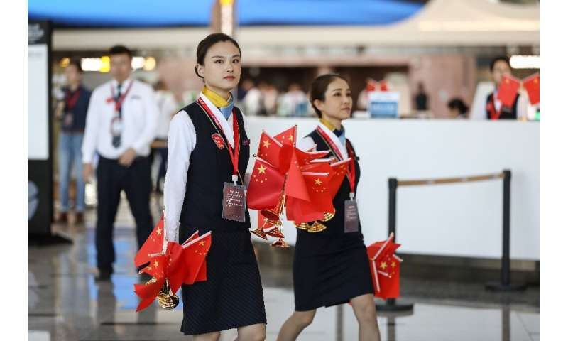 Staffers walk with national flags during the first day of operations at Beijing's new airport, which is seen as an embodiment of