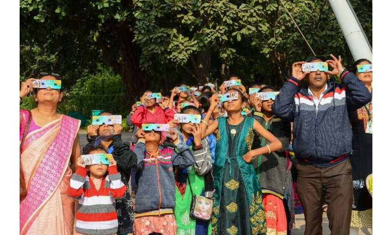"Students and teachers use solar filter glasses to look at the ""ring of fire"" solar eclipse at Gujarat Science City on"