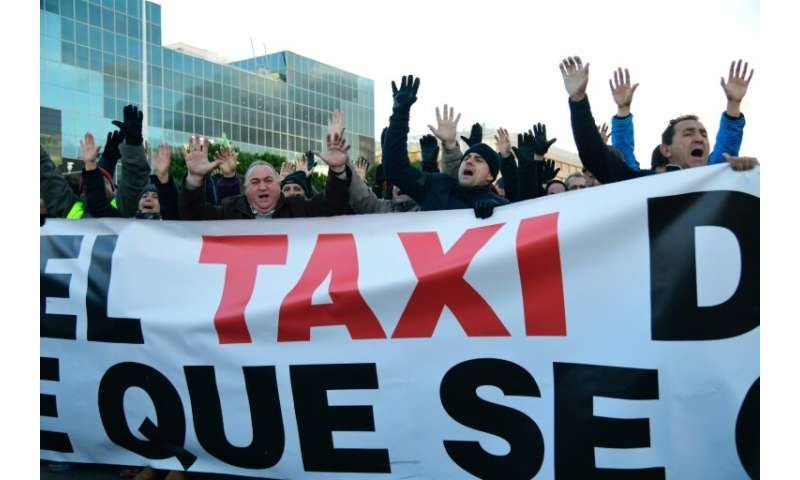 Taxi drivers blocked the road in Madrid outside one of the world's biggest tourism fairs, burning tyres and a dustbin