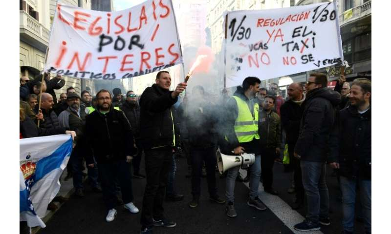 "Taxi drivers hold flares and placards reading ""Regulation now"" during a demonstration in to protest against online rid"