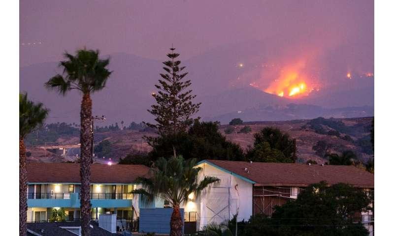 The Cave fire burns a hillside above houses in Santa Barbara, California on November 26, 2019ing homes.
