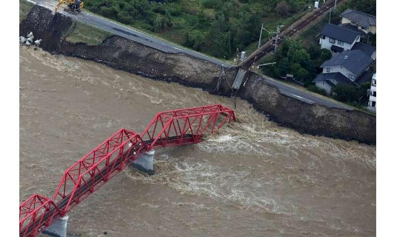 The Chikuma river, heavily swollen by rain from Typhoon Hagibis, swept away part of a train bridge in Ueda, in Japan's Nagano pr