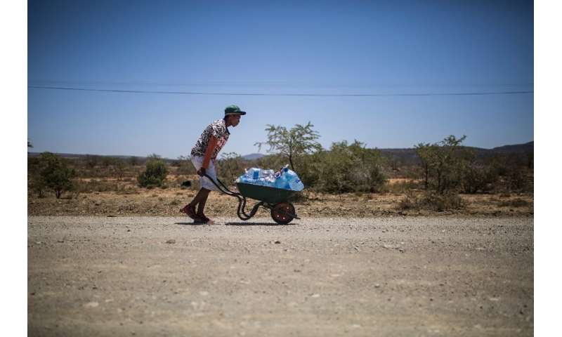 The hot way home: A young man pushes a wheelbarrow with bottles filled with water
