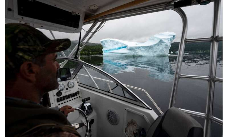 Tour guide and former fisherman Barry Strickland steers his boat near an iceberg at King's Point—iceberg tourism has been a succ