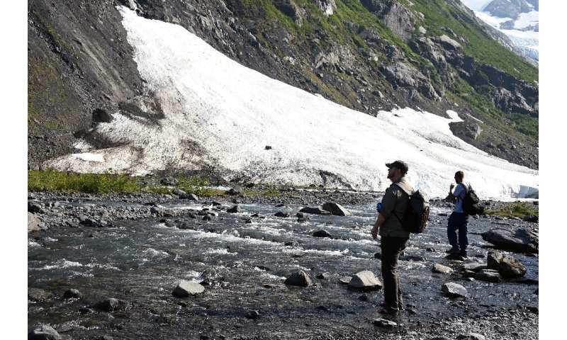 Two hikers take stock of a fast-receding glacier near Portage Lake in Girdwood, Alaska, amid record high temperatures in that no
