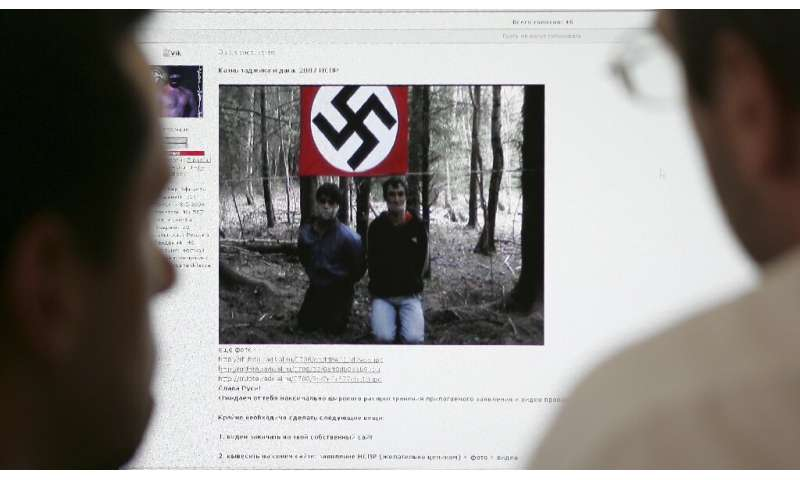 Two men look at the website of the United Slavic National-Socialists Forum on a computer in Moscow in 2007 which contained a vid