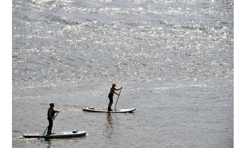 Two women enjoy stand-up paddle-boarding in waters south of Anchorage, Alaska, as the coastal region experiences its highest tem