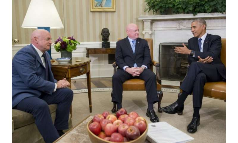 US President Barack Obama meets with NASA astronauts Scott Kelly (C) and his twin brother Mark Kelly in the Oval Office