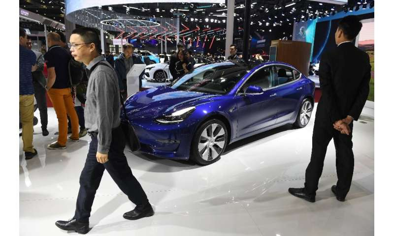 Visitors walk past a Tesla Model 3 at the Shanghai Auto Show in China on April 17, 2019