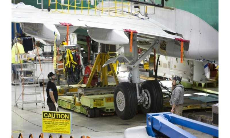 Workers stand under the wing of a Boeing 737 MAX airplane at the company's factory in Renton, Washington