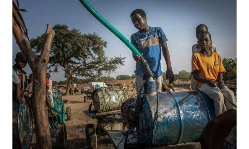 Young hawkers fill barils with water in the Moura wadi in Hadjer Hadid