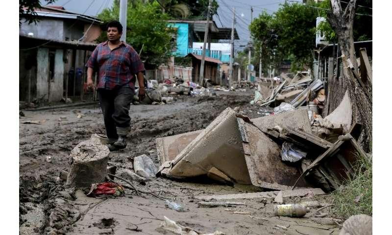 A man walks along a damaged street in La Lima, Honduras as Hurricane Iota approaches