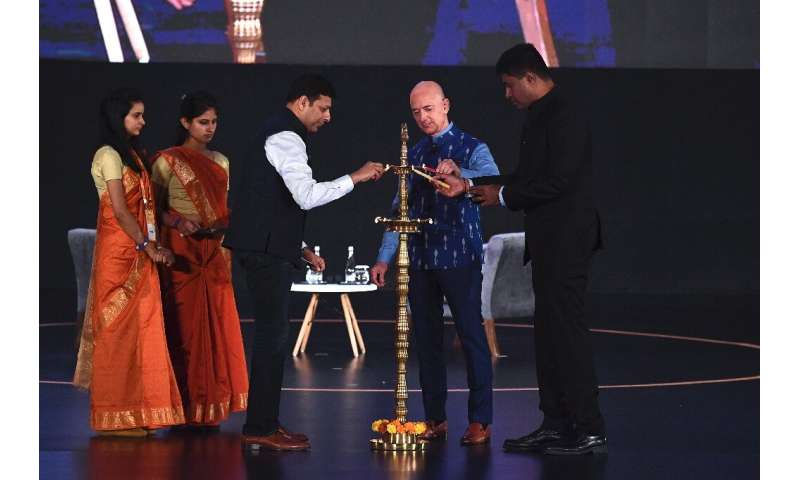 Amazon CEO Jeff Bezos (R) lights a traditional lamp along with Amit Agarwal (3L), senior vice president and country manager for