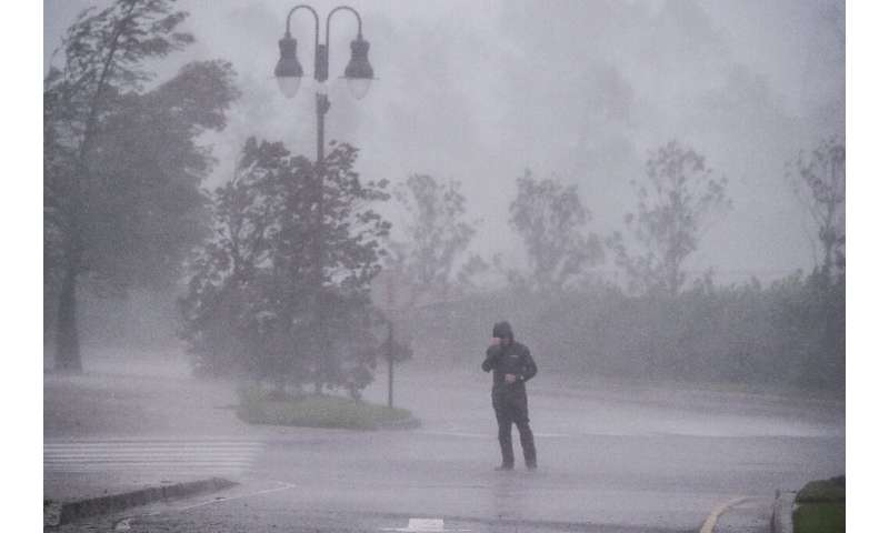 A reporter covers his face as Hurricane Delta makes landfall in Lake Charles, Louisiana on October 9, 2020