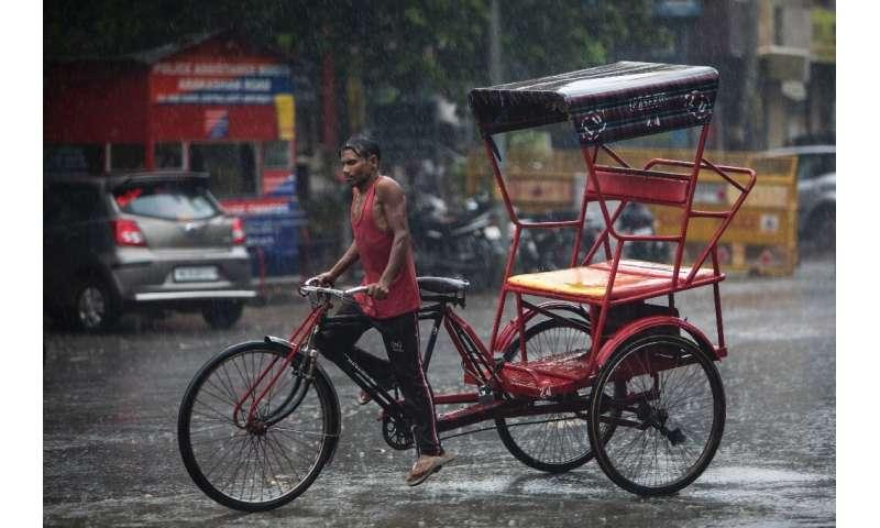 A rickshaw driver rides along a street during monsoon rainfall in New Delhi