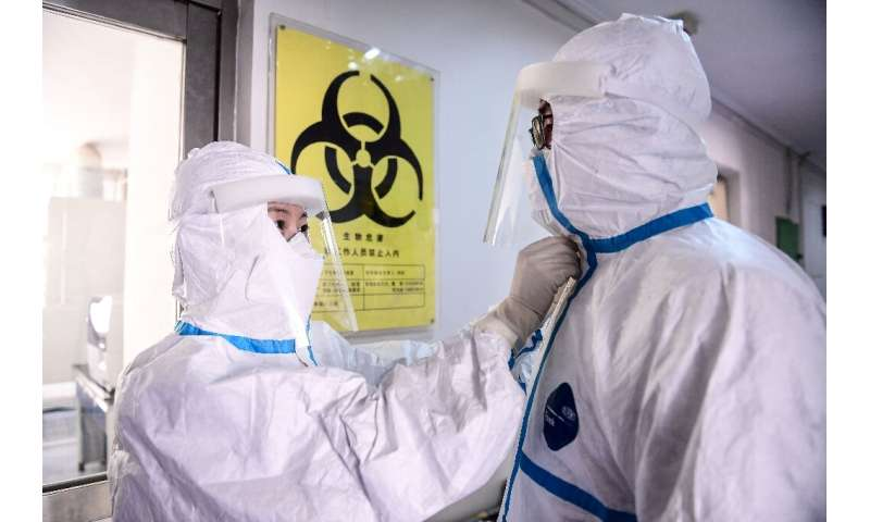 A technician helps a colleague remove a protective suit after leaving a laboratory in Shenyang in China's northeastern Liaoning