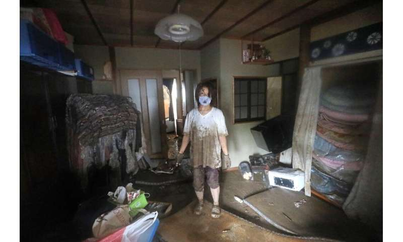 A woman stands in her flood-damaged home in  Hitoyoshi, Kumamoto prefecture