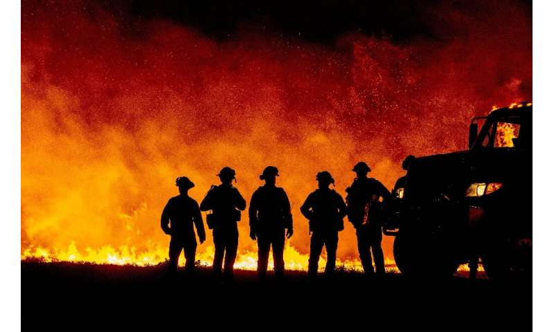 Butte County firefighters watch as flames quickly spread across a road at the Bear Fire in Oroville, California